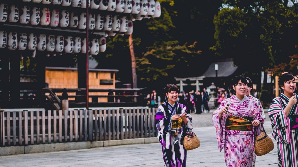 Traditional Japanese lanterns and kimono seen near a town square