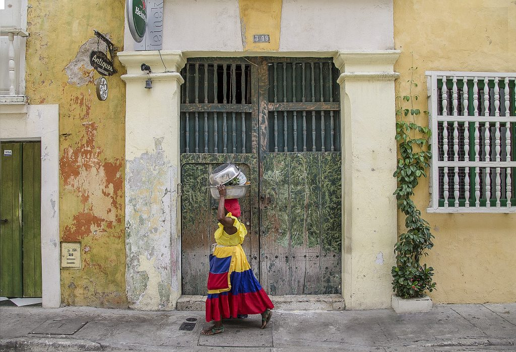 Colombian woman carries market goods down a colonial street